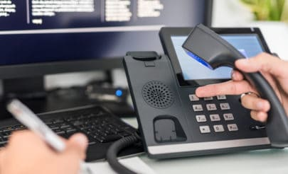 hand-holding-corded-phone-while-dialing-number-at-work-station-desk